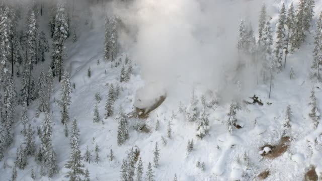 aerial track over steaming hot springs in winter, yellowstone, usa - hot spring stock videos & royalty-free footage