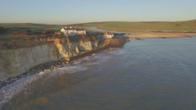 Aerial track past clifftop cottages