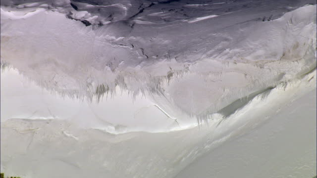 vídeos de stock, filmes e b-roll de aerial track past icicles hanging from snowy mountain ridge, yellowstone, usa - snow cornice