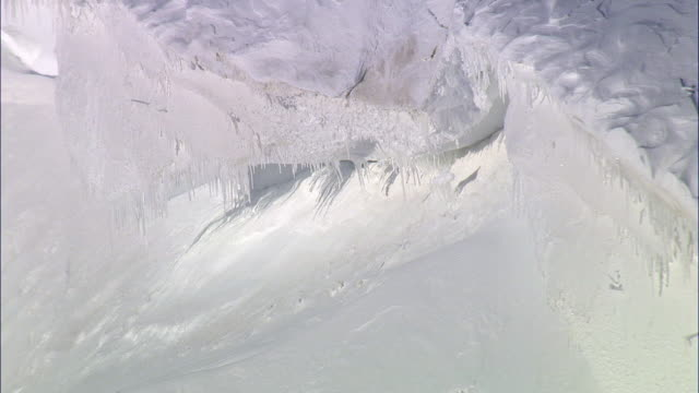 aerial track past icicles hanging from snowy mountain ridge, yellowstone, usa - snow cornice stock videos and b-roll footage