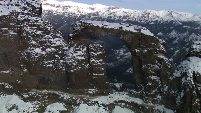 Aerial track past snowy rock arch on mountain ridge, Yellowstone, USA