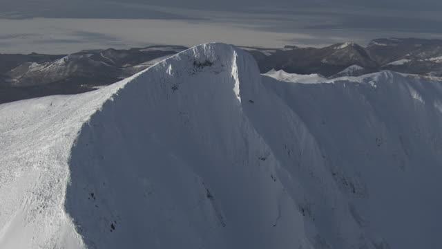 aerial track round snowy ridge. japan. - hokkaido stock videos & royalty-free footage