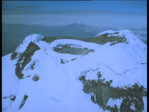 Aerial track towards and over snow capped dormant volcano crater