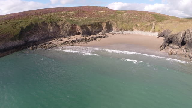 vídeos de stock e filmes b-roll de aerial track towards remote beach on pembrokeshire coast - pembrokeshire