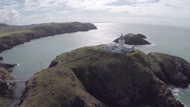 vídeos de stock e filmes b-roll de aerial track towards strumble head lighthouse - pembrokeshire