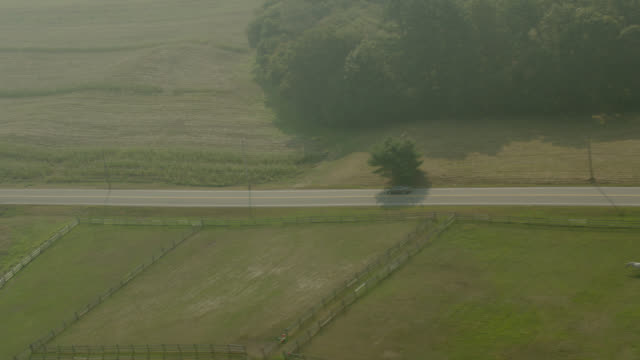 vidéos et rushes de aerial tracking a car driving on country highway or road. trees, grass meadows or pastures. rural area. - route de campagne