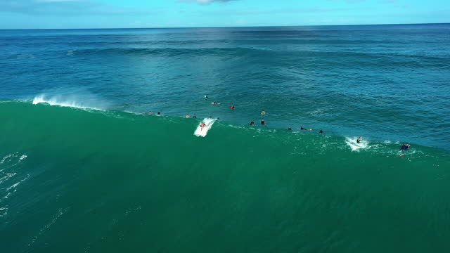 aerial tracking a daring surfer riding a giant crashing wave with bright sunlight, white foaming surf, and other surfers paddling nearby - oahu, hawaii - other点の映像素材/bロール