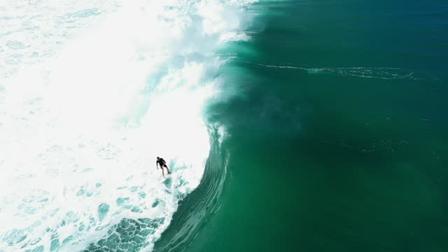 aerial tracking a male surfer riding a giant crashing wave with bright sunlight, white foaming surf, and other surfers paddling nearby - oahu, hawaii - other点の映像素材/bロール