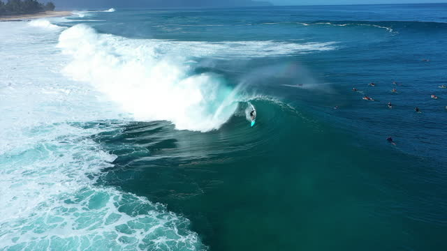 aerial tracking a surfer riding a colossal crashing wave with deep blue ocean water, white foaming surf, and other surfers paddling nearby - oahu, hawaii - other点の映像素材/bロール