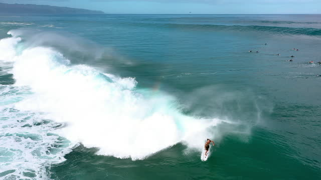 aerial tracking a surfer riding a monstrous crashing wave with deep blue ocean water, white foaming surf, and other surfers paddling nearby - oahu, hawaii - other点の映像素材/bロール