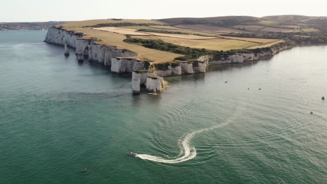 aerial tracking and panning shot showing a motorboat rounding old harry rocks, dorset, england, united kingdom - rock face stock videos & royalty-free footage