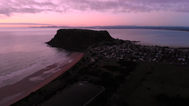4K aerial tracking away from The Nut, towering over the picturesque town of Stanley at dawn on the far north western coast of Tasmania