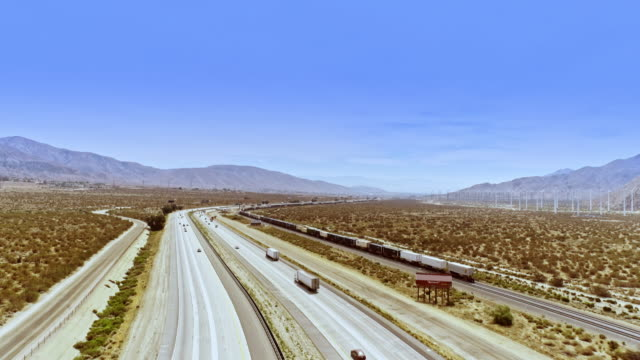 ws aerial tracking from mile long freight train across empty frontage road to heavy freeway traffic on busy interstate 10 and large wind farm in far distance - interstate 10 stock videos & royalty-free footage