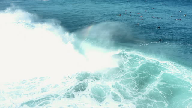 aerial tracking of a surfer on a bodyboard as he rides a large crashing wave with other surfers paddling in the background - oahu, hawaii - other点の映像素材/bロール