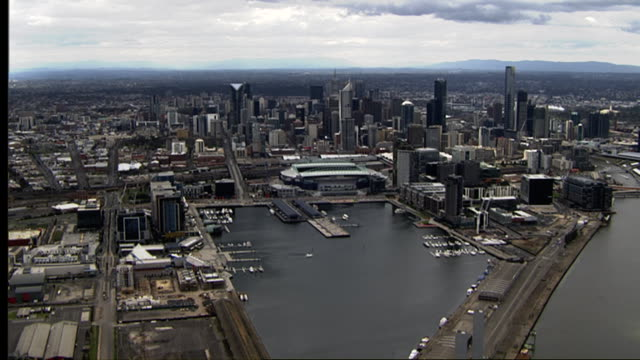 Aerial tracking over Bolte Bridge and docklands towards Melbourne CBD Skyline including Docklands Stadium Southgate Yarra River Close up of Eureka...