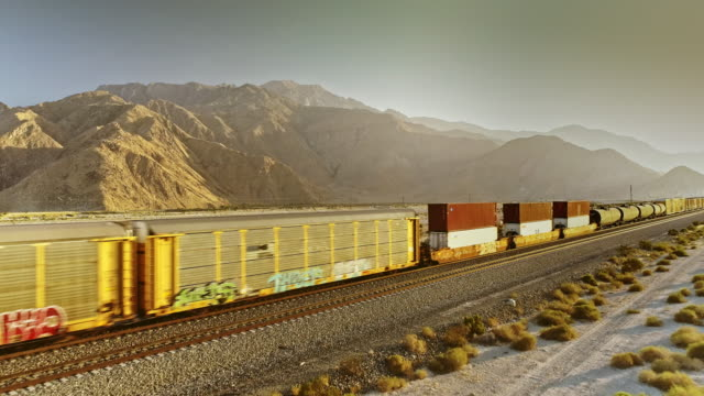 vidéos et rushes de ws aerial tracking over freight train with five diesel engines hauling cargo in unmarked freight cars through sandy southern california desert terrain against san gorgonio mountains - long