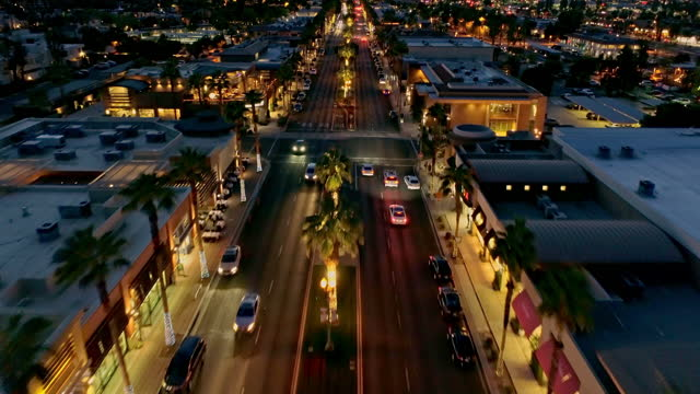 aerial tracking over rooftops and street traffic in downtown palm desert shopping and nightlife district at dusk - street name sign stock videos & royalty-free footage