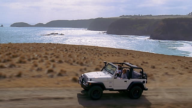 Aerial tracking shot 2 women driving jeep uphill next to water / Flinders, Mornington Peninsula, Australia