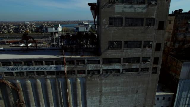 vidéos et rushes de aerial tracking shot along abandoned factory in montreal port - montréal