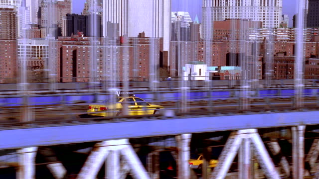 Aerial tracking shot along Manhattan Bridge with taxi in foreground / Manhattan, NYC