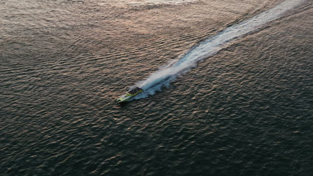aerial tracking shot at sunset showing a powerboat in the ocean, miami, florida, united states of america - miami dade county stock videos & royalty-free footage