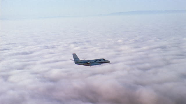 Aerial tracking shot jet flying over mountains and clouds