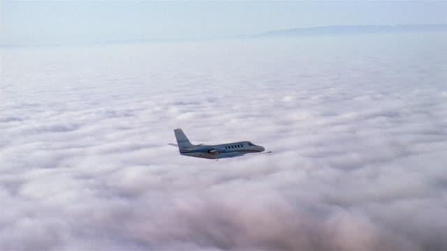 vídeos y material grabado en eventos de stock de aerial tracking shot jet flying over mountains and clouds - toma aérea en vuelo