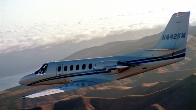 aerial tracking shot jet flying over mountains towards ocean - private jet stock videos & royalty-free footage