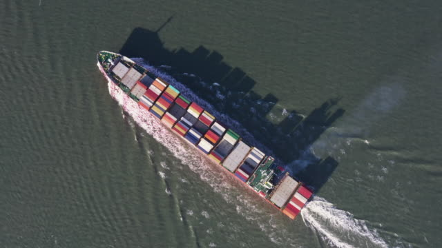 aerial tracking shot looking down on a small cargo vesse and its shadowl in the scheldt river, netherlands - industrial ship stock videos & royalty-free footage