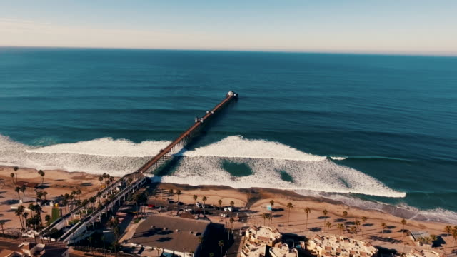 aerial tracking shot of a beautiful sunrise sparkling off the ocean as the pier is revealed. - surf stock videos & royalty-free footage