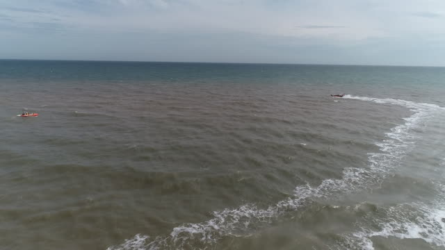 aerial tracking shot of a lifeboat off the coast of hornsea - rescue worker stock videos & royalty-free footage