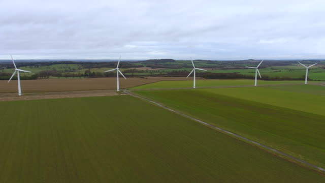 aerial tracking shot of a row of wind turbines - environmental issues stock videos & royalty-free footage
