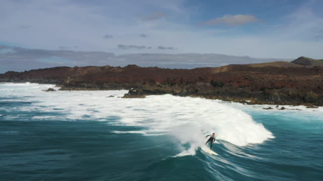 vídeos de stock e filmes b-roll de aerial tracking shot of a surfer riding a wave with a volcanic backdrop, lanzarote, spain - turismo