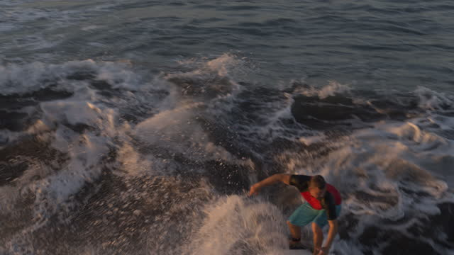 aerial tracking shot of distant man surfing on ocean waves at sunset / san blas, la libertad, el salvador - using a paddle stock videos & royalty-free footage