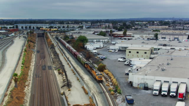 aerial tracking shot of freight train on the alameda corridor, los angeles - rail freight stock videos and b-roll footage