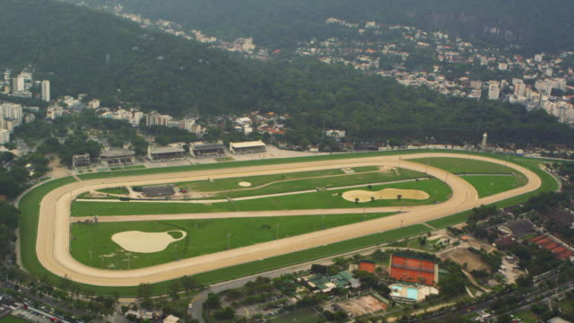 aerial tracking shot of jockey club brazileiro in rio de janeiro, brazil - pferderennbahn stock-videos und b-roll-filmmaterial
