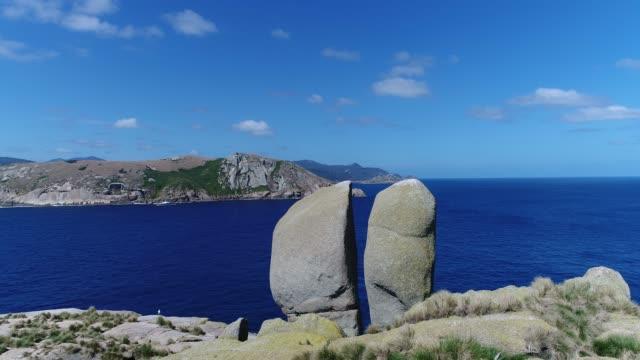 vídeos y material grabado en eventos de stock de 4k aerial tracking shot of massive boulders within seascape - brightly lit