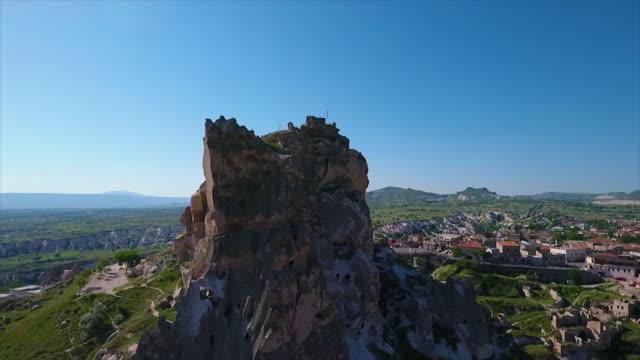 vídeos de stock e filmes b-roll de aerial, tracking shot of petruding rock and town - exposto ao ar