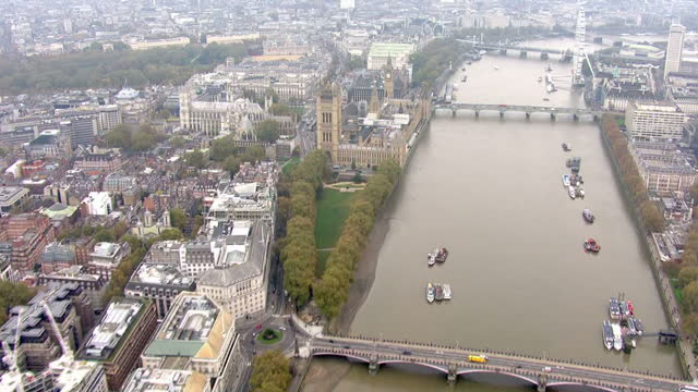Aerial tracking shot of the Thames showing the Houses of Parliament London Eye and The SIS Building or MI6 Building at Vauxhall Cross houses the...