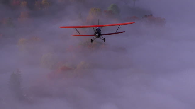 aerial tracking shot point of view red biplane flying over trees and fog in autumn / new england - biplane stock videos & royalty-free footage