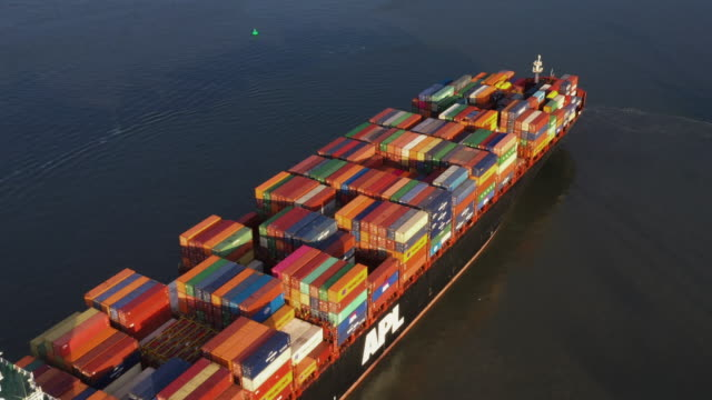 aerial tracking shot showing a container ship sailing in a river, netherlands - on the move stock videos & royalty-free footage