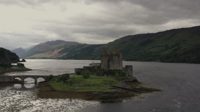 aerial tracking shot showing eilean donan castle and surrounding landscape, scottish highlands, united kingdom - lakeshore stock videos & royalty-free footage