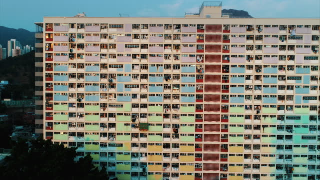 aerial tracking shot showing the colourful facade of an apartment complex in choi hung estate, hong kong - block shape stock videos & royalty-free footage