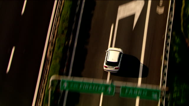 Aerial tracking shot zoom out white sedan driving on motorway between Rome and Florence / Italy