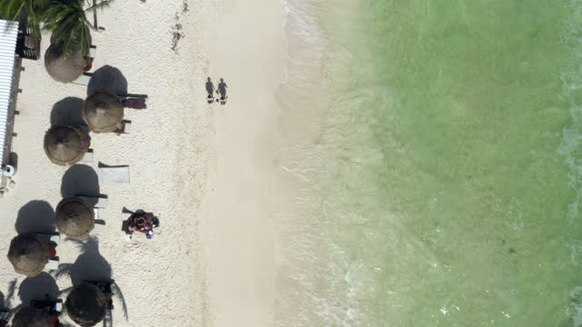 aerial tracking two people as they walk along a beautiful caribbean beach shoreline, with bright sunlight, gleaming sand, and crashing waves - tulum, mexico - village点の映像素材/bロール
