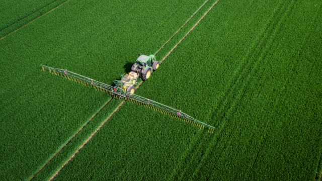 aerial: tractor spraying fertilizer on fields - agricultural machinery stock videos & royalty-free footage
