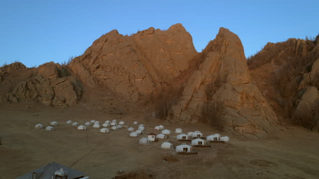 aerial: traditional white mongolian gers on field against rocky mountains - northern countryside, mongolia - 村点の映像素材/bロール