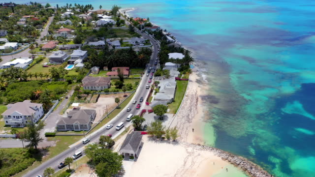 vidéos et rushes de aerial: traffic along waterfront road near beach and neighborhood - nassau, bahamas - bahamas