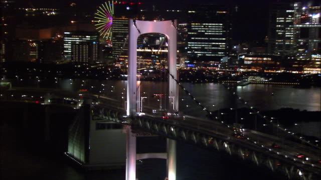 Aerial traffic on Rainbow Bridge/ zoom out traffic on bridge and skyline/ circling bridge tower/ zoom out skyline/ Tokyo / November 16, 2005