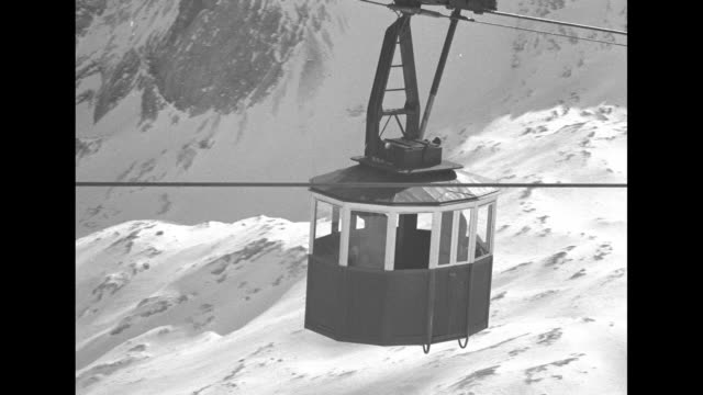 aerial trams going up and down mountain over snowy landscape, mountains of the bavarian alps in background / pan across mountains / two shots from... - baviera video stock e b–roll